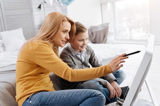 Olhe aqui. mulher jovem e simpática segurando uma caneta stylus e apontando para a tela digital enquanto está sentada com seu filho na frente dela