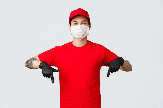 Olhe aqui. sério, confiante entregador asiático com braço tatuado, apontando os dedos para baixo para mostrar a promoção de propaganda em luvas de proteção e máscara médica. correio vestindo uniforme, encomendas de entrega