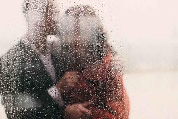 Olhe através da janela molhada no casal abraçando