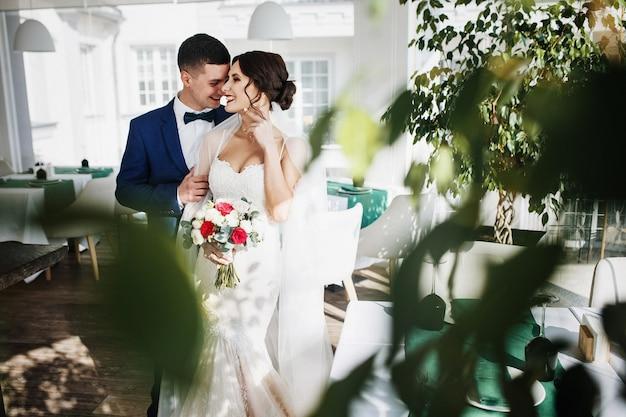 Olhe através da vegetação no casal de noivos em pé no corredor