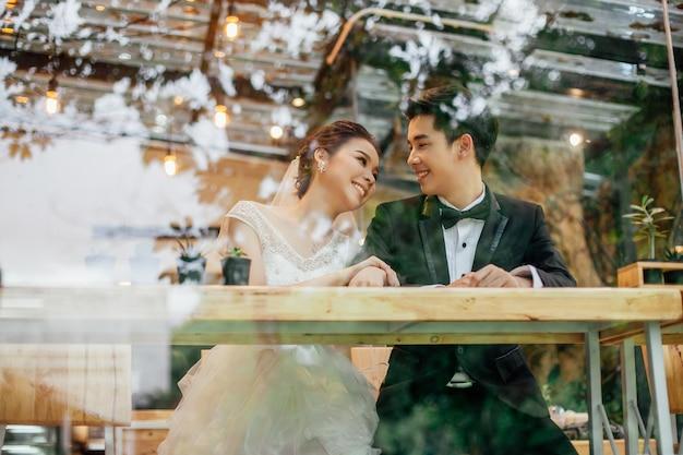 Olhe através do vidro do restaurante. há uma noiva asiática e uma noiva asiática conversando com rostos sorridentes.