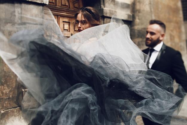 Olhe de baixo para uma mulher maravilhosa com um vestido rico preto e cinza