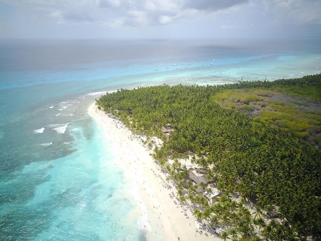 Olhe de cima em água turquesa ao longo da praia dourada em algum lugar da república dominicana