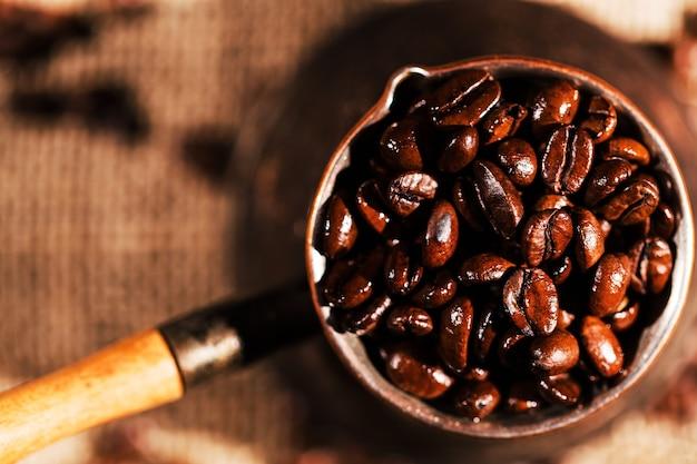 Olhe de cima em grãos de café em um cezve