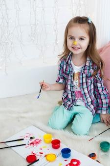 Olhe de cima na menina encantadora que joga com as pinturas azuis, vermelhas e amarelas no assoalho