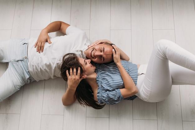 Olhe de cima para homem e mulher em roupas azuis e brancas deitado