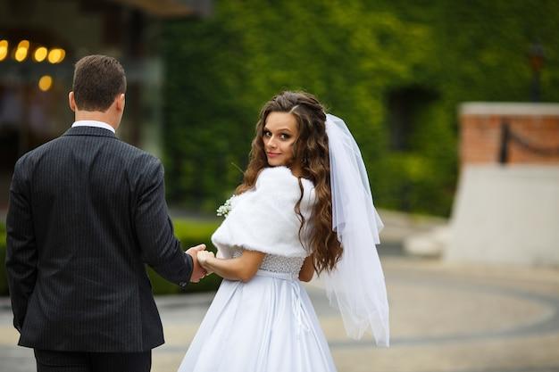Olhe de trás para a noiva e o noivo andando no quintal