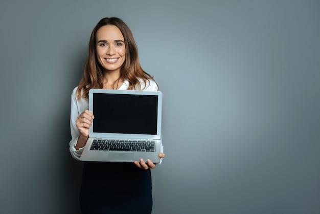 Olhe para a tela. mulher bonita e atraente segurando seu laptop e sorrindo enquanto o mostra a você