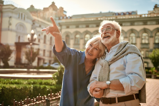Olhe para aquela mulher sorridente sênior apontando para longe e mostrando algo para seu marido enquanto gastava
