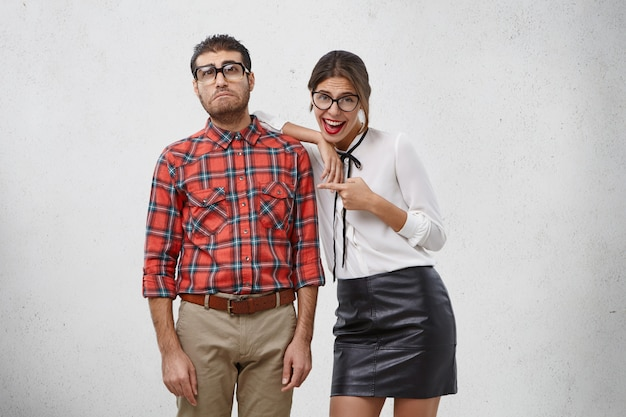 Olhe para ele! modelo feminino bonito e alegre se inclina sobre o ombro do melhor amigo geek e aponta para ele