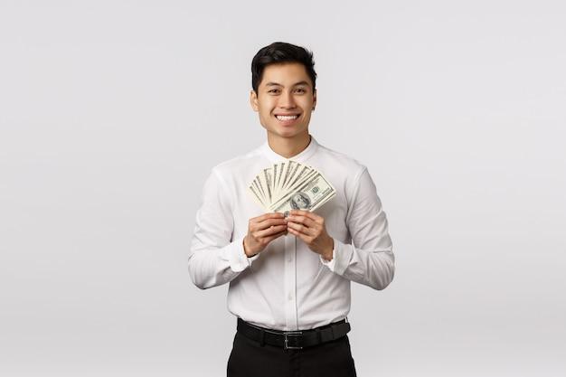 Olhe para esse dinheiro. feliz e rico rapaz asiático jovem bonito pronto gastar salário em compras, segurando o dinheiro e sorrindo, ganhando esporte lance, alcançar a escada corporativa de sucesso
