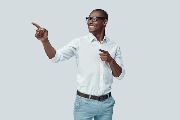 Olhe para lá! africano jovem e bonito apontando para o espaço da cópia e sorrindo em pé contra um fundo cinza