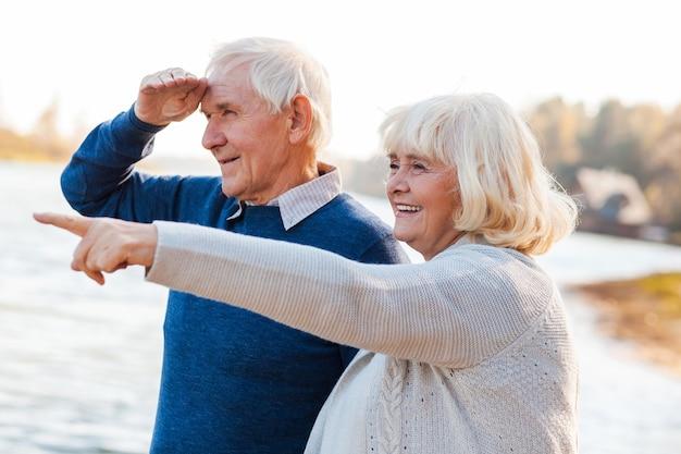 Olhe para lá! casal de idosos felizes em pé no cais juntos enquanto uma mulher apontando e sorrindo