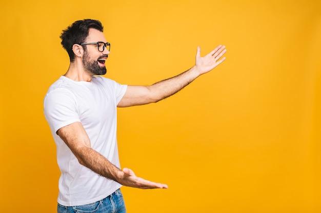 Olhe para lá! homem bonito jovem feliz em casual apontando para copyspace e sorrindo em pé isolado sobre fundo amarelo.