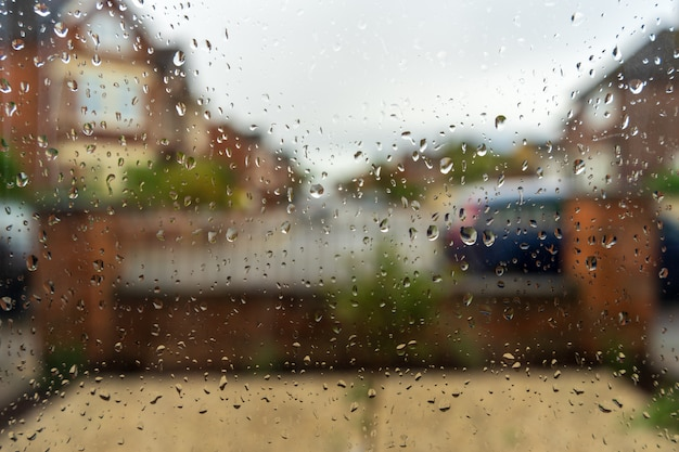 Olhe para o rosto do outono através do vidro da janela coberto por gotas de chuva