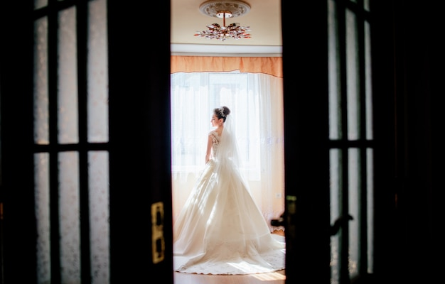 Olhe por trás da porta em uma linda noiva de pé em um quarto de hotel de luxo