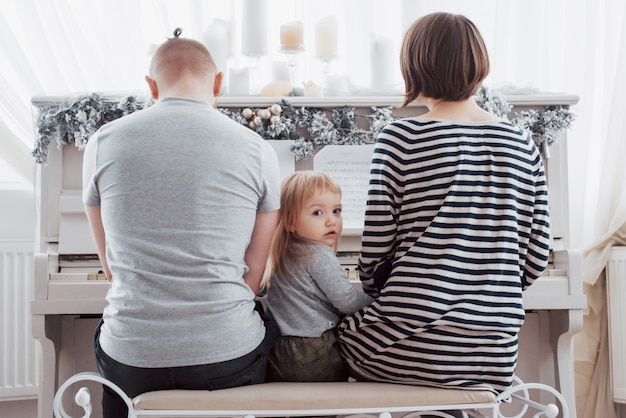 Olhe por trás para mãe pai e filha tocando piano branco