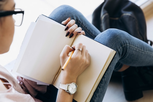 Olhe sobre o ombro da menina enquanto ela escreve algo no notebbook