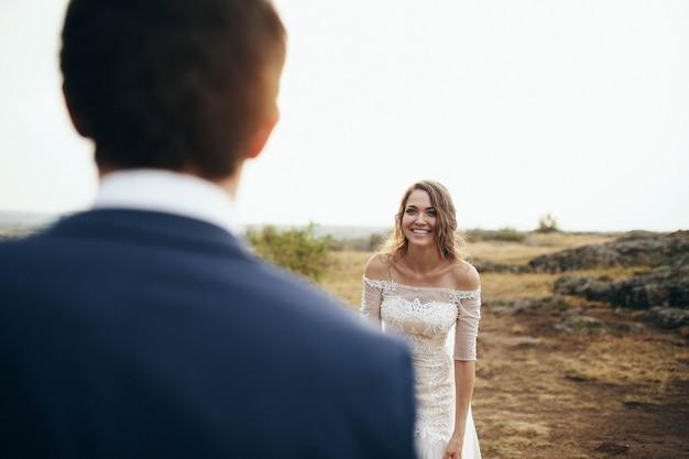 Olhe sobre o ombro do noivo e a noiva sorridente no campo