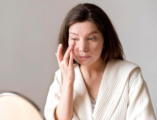Olho aplicando feminino concelear com a mão