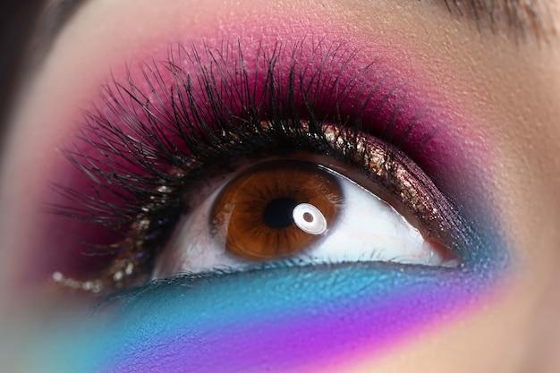 Olho castanho bonito com maquiagem brilhante olha para cima