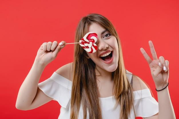Olho de cobertura de mulher com doces pirulito em forma de coração, vestindo blusa branca isolada na parede vermelha