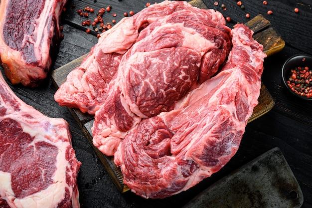Olho de costela de carne crua de corte espesso. conjunto de bife de lombo de carne orgânica em mármore, em mesa de madeira escura