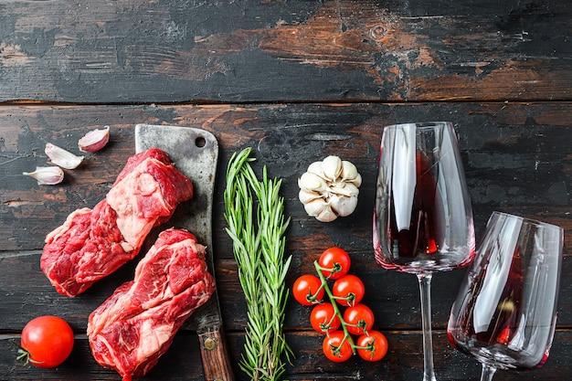 Olho de mandril cru orgânico rolar bife sobre velho cutelo de açougueiro perto de taças de vinho tinto com ervas e temperos na velha mesa de madeira escura. vista superior, com espaço para texto.