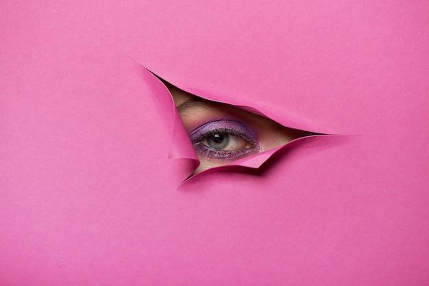 Olho de menina com maquiagem em um buraco de papel rosa rasgado.