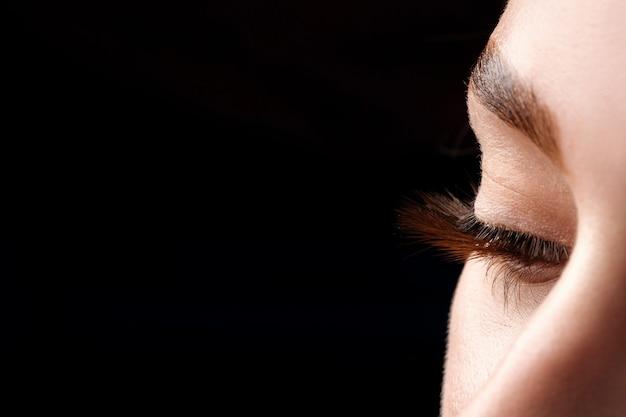 Olho de mulher bonita macro com cílios extremamente longos e maquiagem natural
