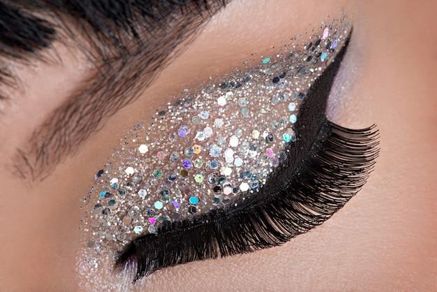 Olho de mulher com bela maquiagem brilhante fashion