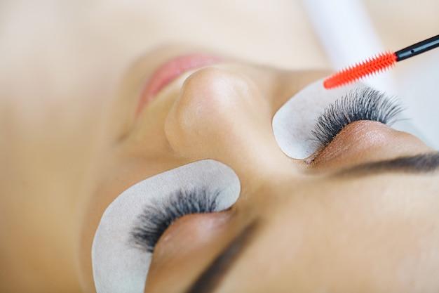 Olho de mulher com cílios longos. escova de rímel.
