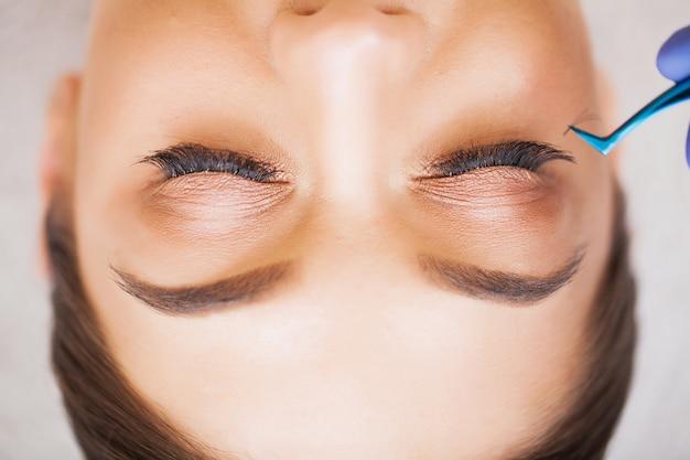 Olho de mulher com cílios longos. mulher jovem e bonita durante a extensão dos cílios