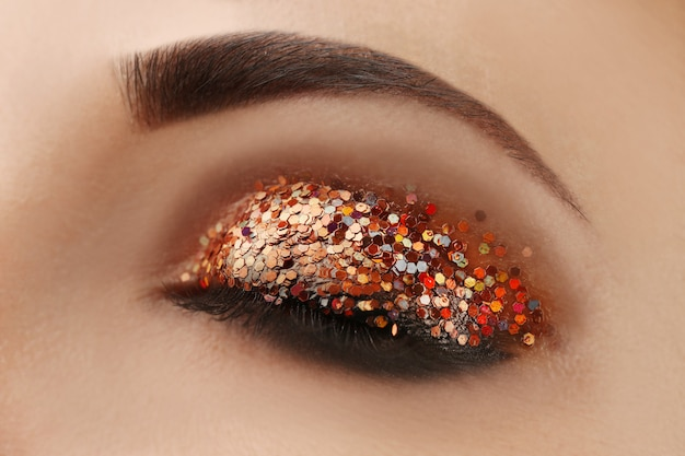 Olho de mulher com maquiagem brilhante, visão macro