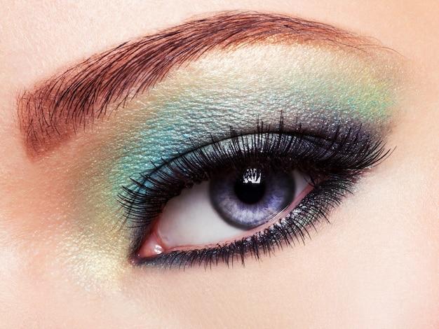 Olho de mulher com maquiagem de olhos verdes