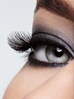 Olho de mulher com maquiagem preta. imagem de estilo macro. cílios longos