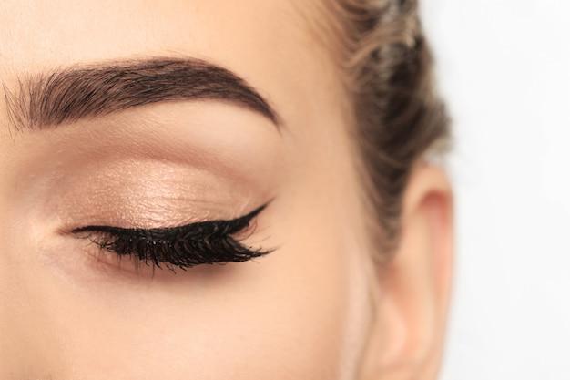 Olho de mulher jovem com uma sobrancelha bonita após a correção, close-up