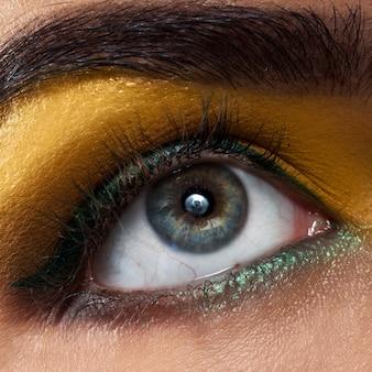 Olho de mulher macro com maquiagem amarela em estúdio