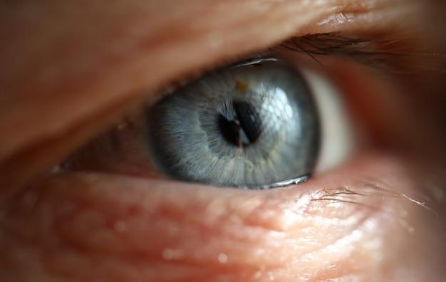 Olho direito cinzento azul masculino na técnica de pouca luz