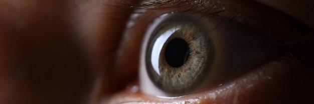 Olho esquerdo masculino de cor verde cinza em close-up de técnica com pouca luz
