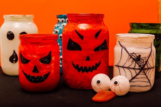 Olhos artificiais e língua estão ao lado de latas com abóbora e teias de aranha em uma mesa preta