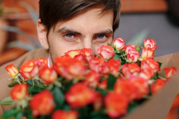 Olhos azuis de homem close-up através de um buquê de flores