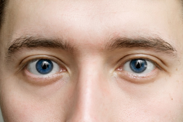 Olhos azuis de um homem de perto. o conceito de óptica oftalmológica e medicina. o olhar masculino