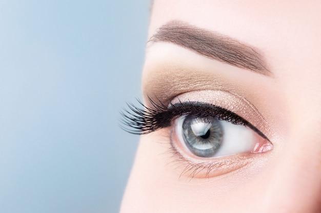 Olhos azuis fêmeas com pestanas longas, close-up bonito da composição.