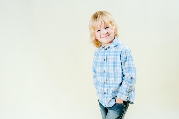 Olhos azuis incríveis e inocência de cabelos louros bonitos de um menino de 5 anos. retrato simples, que está vestindo uma camisa azul