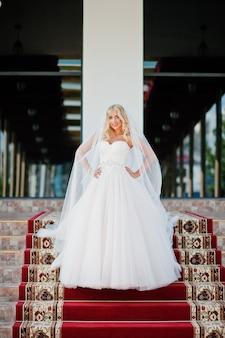 Olhos azuis loiros elegantes moda noiva no grande salão de festas no tapete vermelho