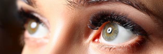 Olhos de cor verdes femininos incríveis com close-up de extensões de cílios