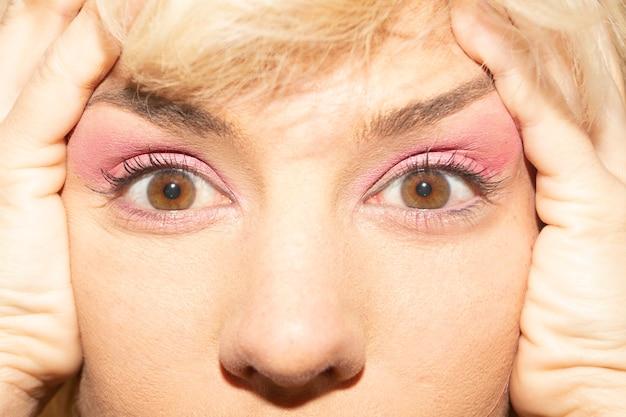 Olhos de mel de mulher estendidos com as mãos