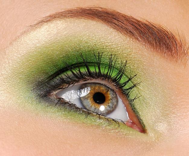 Olhos de mulher com cor verde brilhante de cosmético para sombra