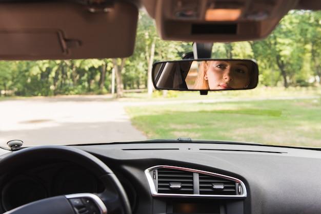 Olhos de mulher no espelho do carro